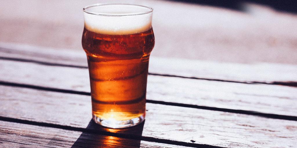 Vue d'une pinte de bière blonde posée au soleil sur l'une des tables en bois de la terrasse du Lenox Pub