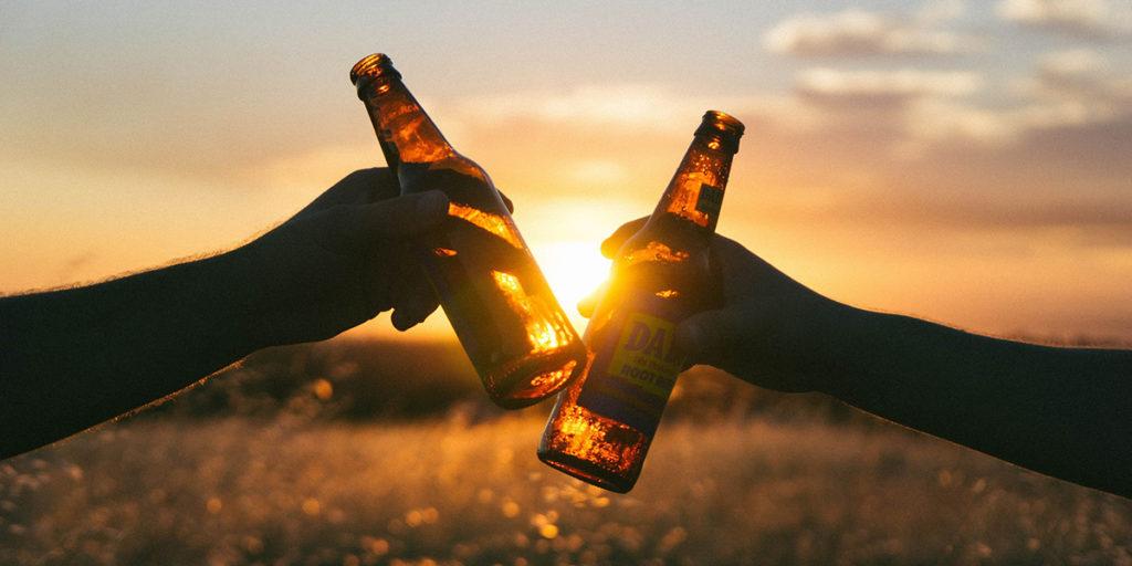 """Deux personnes font un """"cheers"""" avec les bouteilles de bières devant un soleil couchant"""